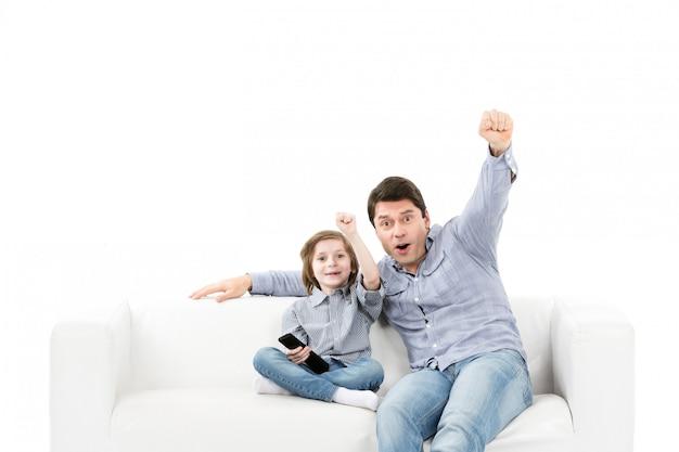 Отец и сын эмоционально смотрят игру в комнате