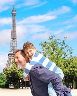 Отец и сын наслаждаются друг другом на фоне эйфелевой башни в париже.