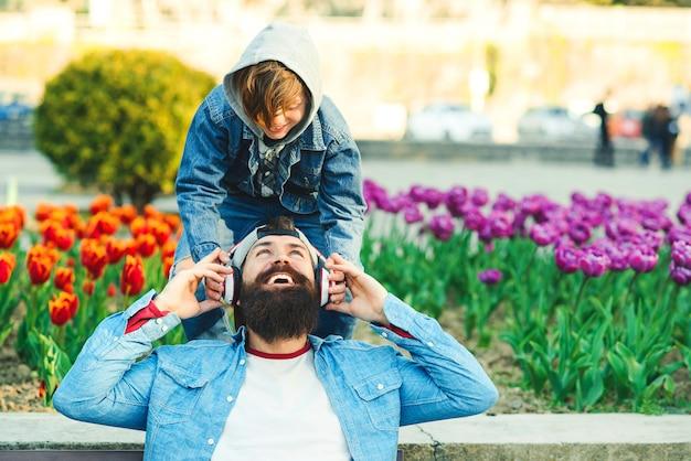 Отец и сын, наслаждаясь музыкой на открытом воздухе. молодой отец с помощью беспроводных наушников слушать музыку.