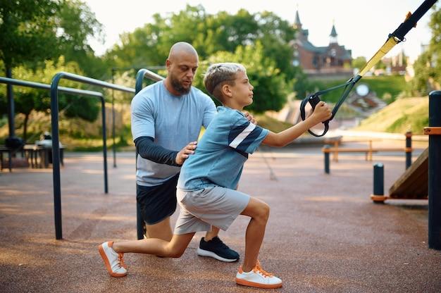 父と息子、ロープを使った運動、屋外の遊び場でのスポーツトレーニング。家族は夏の公園で健康的なライフスタイル、フィットネストレーニングをリードしています