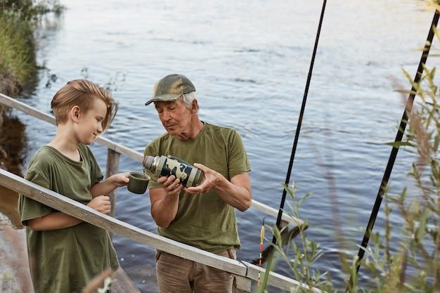 Отец и сын ловят рыбу в реке