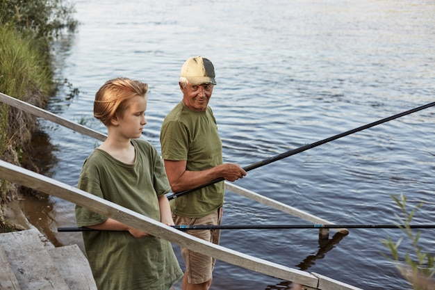 父と息子の手に棒がある木製の階段で釣り、お父さんが愛で彼の少年を見て、家族が野外で一緒に時間を過ごす、緑のtシャツを着ている男。