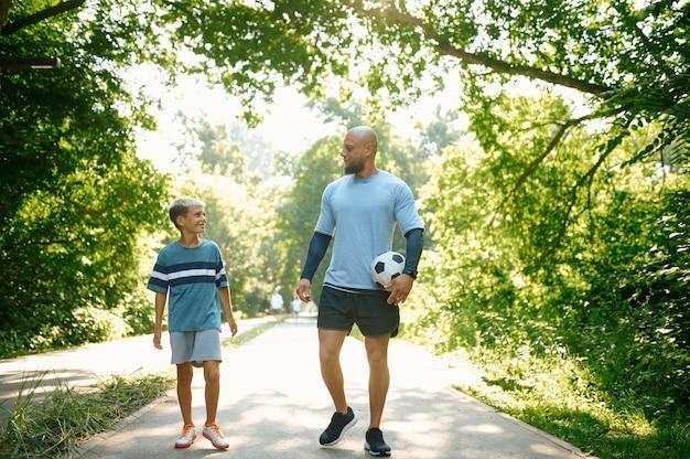 父と息子、屋外の散歩道のサッカー選手。家族は健康的なライフスタイルをリードし、夏の公園でパパとボールを持った少年