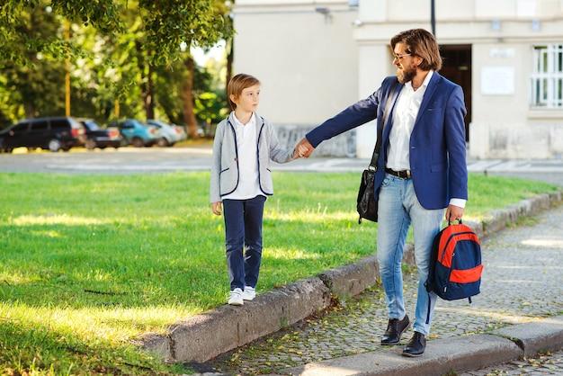 Отец и сын ходят в школу. снова в школу концепции.