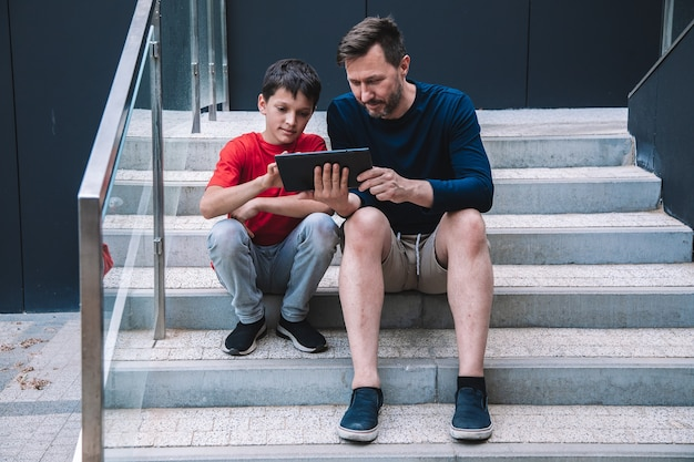 Отец и сын прекрасно проводят время, играя вместе на планшете. современные технологии. стиль жизни. фото высокого качества