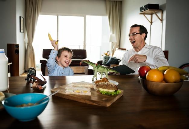 朝食のテーブルで楽しんでいる父と息子