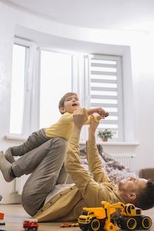 Отец и сын веселятся в гостиной