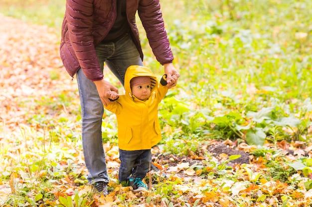 Отец и сын веселятся на свежем воздухе на осенней природе