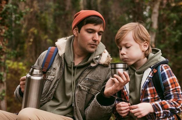 Отец и сын пьют горячий чай на открытом воздухе на природе