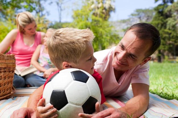 背景で読書する家族とサッカーボールを持つ父と息子