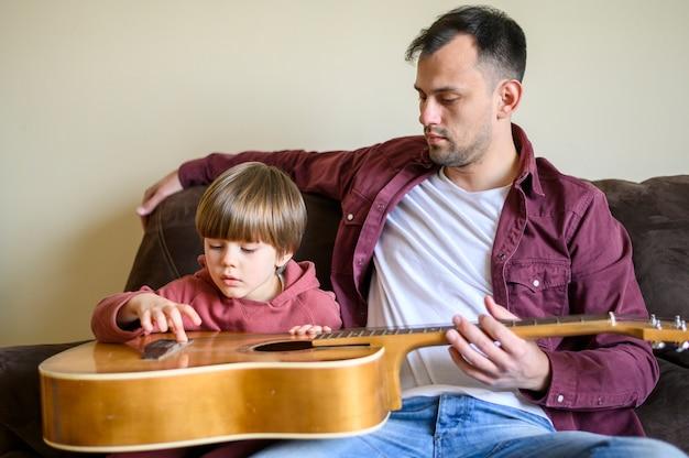 Отец и сын держат гитару
