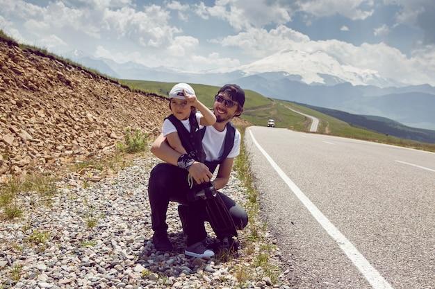 모자와 선글라스를 쓴 아버지와 아들은 산에서 길에 서있는 차를 잡습니다.