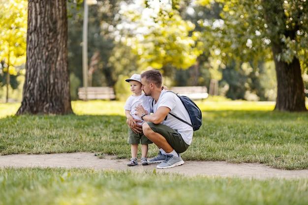 自然の中で父と息子。お父さんは男の子の隣にしゃがんで、晴れた日に森の中にいる間に何かを彼に話します。同じカジュアルな服を着て、週末を一緒に公園で過ごします