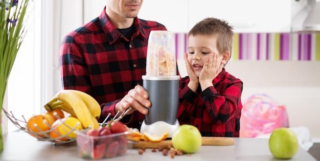 同じシャツを着た父と息子はブレンダーが完了するのを待っているので、明るいキッチンでスムージーを食べることができます。