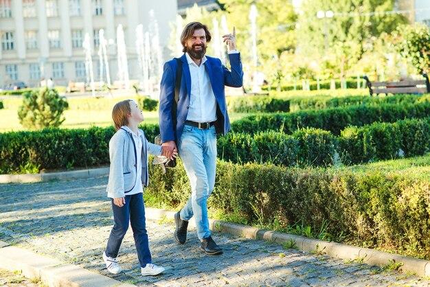 Отец и сын в костюмах гуляют по улице города. стильные папа и малыш идут рука об руку.