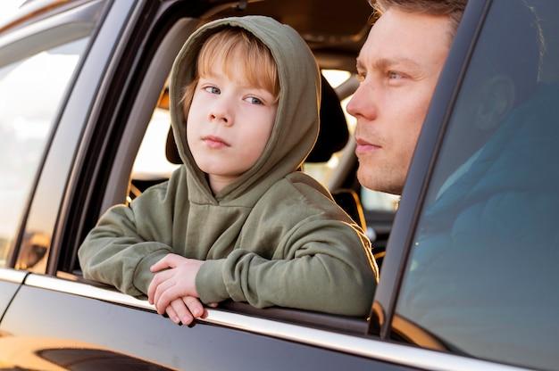 도로 여행을하는 동안보기를 감탄하는 차에있는 아버지와 아들