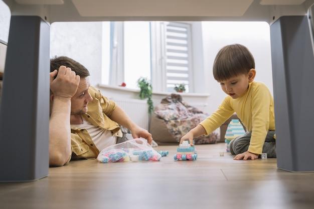 Отец и сын в гостиной под столом низкий вид