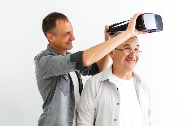 Отец и сын в виртуальных очках, изолированная белая стена.