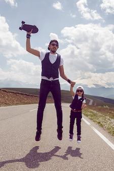 아버지와 아들은 여름에 에베레스트 산을 배경으로 도로에서 검은 스케이트 보드로 점프합니다.
