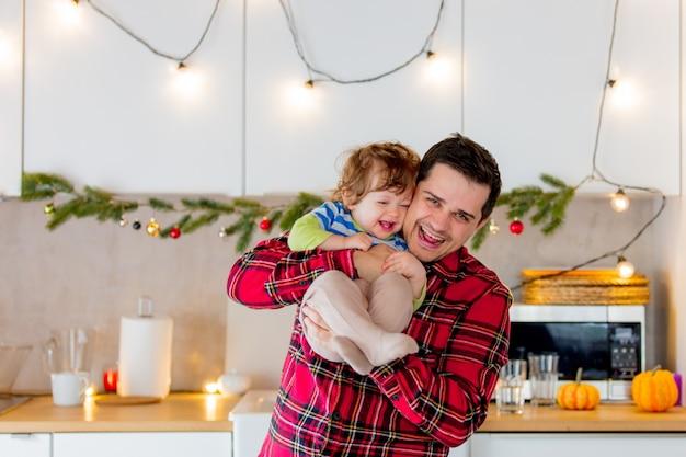 아버지와 아들이 크리스마스 장식과 함께 부엌에서 웃고