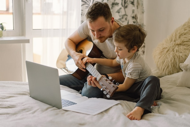 父と息子はオンラインレッスンでアコースティックギターを弾くことを学びます。