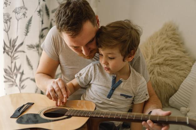 アコースティックギターの弾き方を学ぶ父と息子。