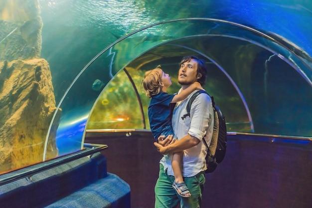 Отец и сын смотрят на рыбок в аквариуме в океанариуме.