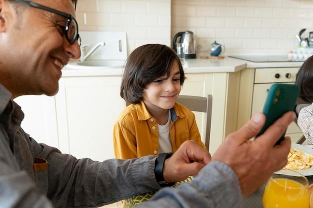 Отец и сын, глядя на смартфон дома