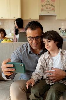 家でスマートフォンを見ている父と息子
