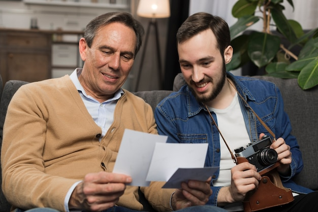 Отец и сын смотрят на фотографии
