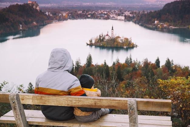 スロベニアヨーロッパのブレッド湖の秋または冬の素晴らしい景色と夕日を探している父と息子