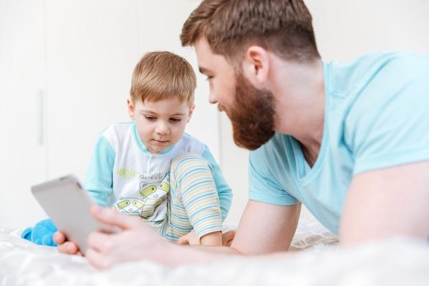 父と息子が横になって、家でタブレットで遊んでいます
