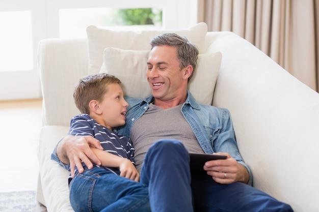 父と息子のリビングルームでデジタルタブレットでソファーに横になっています。