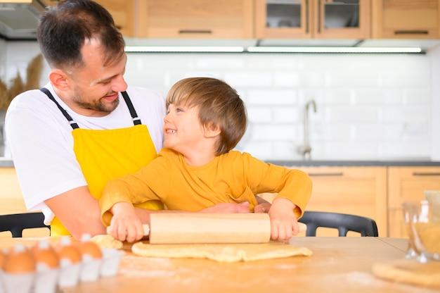 Отец и сын делают тесто с веслом