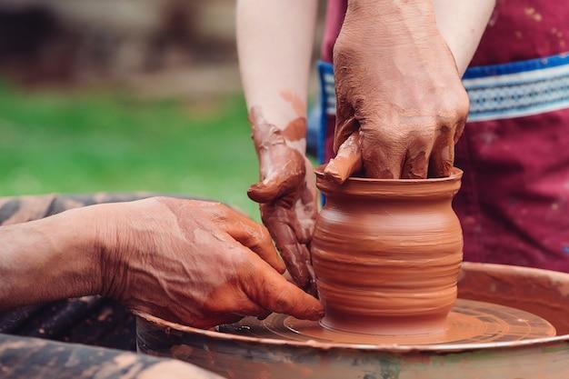 父と息子がセラミックポットを作っています。ろくろに取り組んでいる家族。陶芸家と子供の手。外の陶芸工房