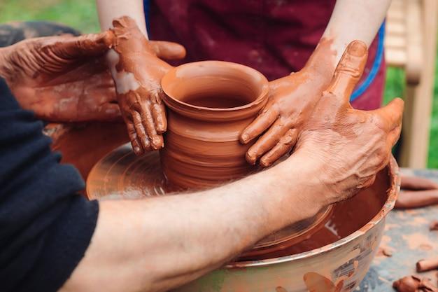父と息子がセラミックポットを作っています。ろくろに取り組んでいる家族。陶芸家と子供の手。