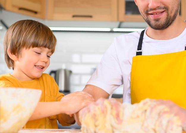 Отец и сын делают тесто крупным планом