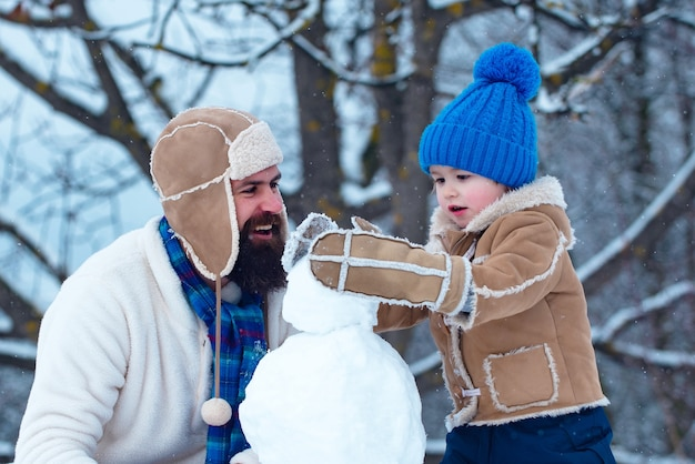 아버지와 아들 눈 속에서 눈사람 만들기. 수제 재미있는 눈사람. 크리스마스 휴일 및 겨울 신작