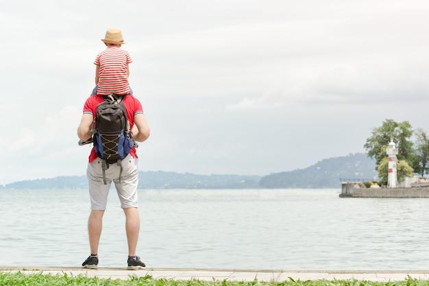 Отец и сын на плечах стоят на пирсе, маяке и на расстоянии горы вид сзади