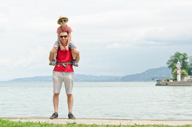 Отец и сын на плечах стоят на пирсе на фоне моря, маяка и гор на расстоянии