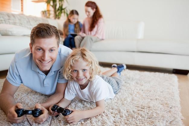床に父と息子がビデオゲームをする