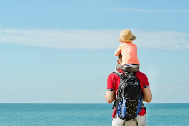 Отец и сын на плечах стоят на берегу моря, вид сзади