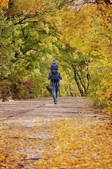 父と息子が肩を組んで秋の公園を散歩します。背面図