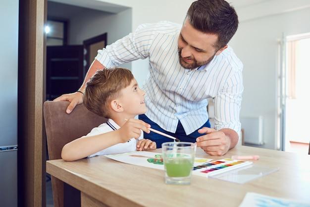 父と息子は部屋のテーブルで紙にペイントします
