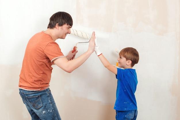 Отец и сын красят стену. молодая семья рисует стену дома.