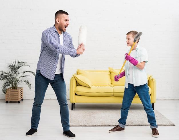 Отец и сын играют в бой с тряпкой и метлой