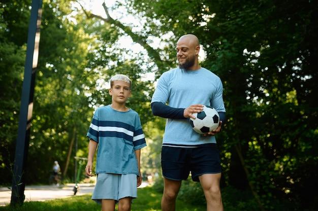 父と息子は晴れた日に屋外でサッカーをします。家族は夏の公園で健康的なライフスタイル、朝のフィットネストレーニングをリードしています