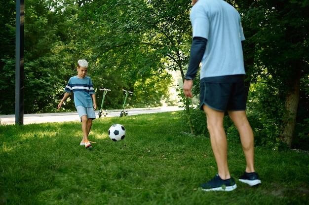 父と息子は屋外の芝生でサッカーをします。家族は夏の公園で健康的なライフスタイル、朝のフィットネストレーニングをリードしています