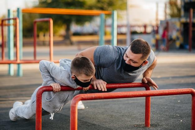 아버지와 아들은 일몰 동안 마스크에 스포츠 분야에서 스포츠를 재생합니다. 건강한 육아와 건강한 생활 방식.