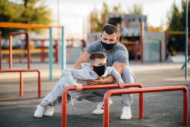 Отец и сын занимаются спортом на спортивной площадке в масках во время заката